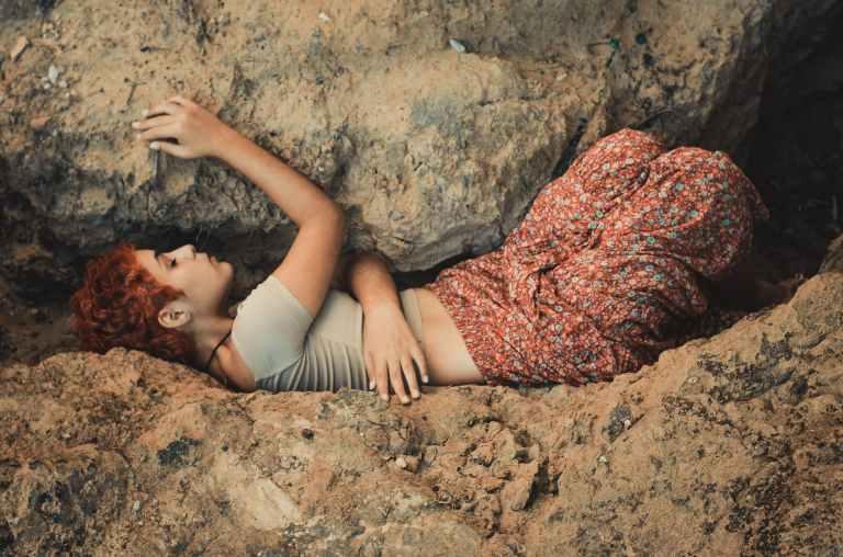 woman lying in between boulders