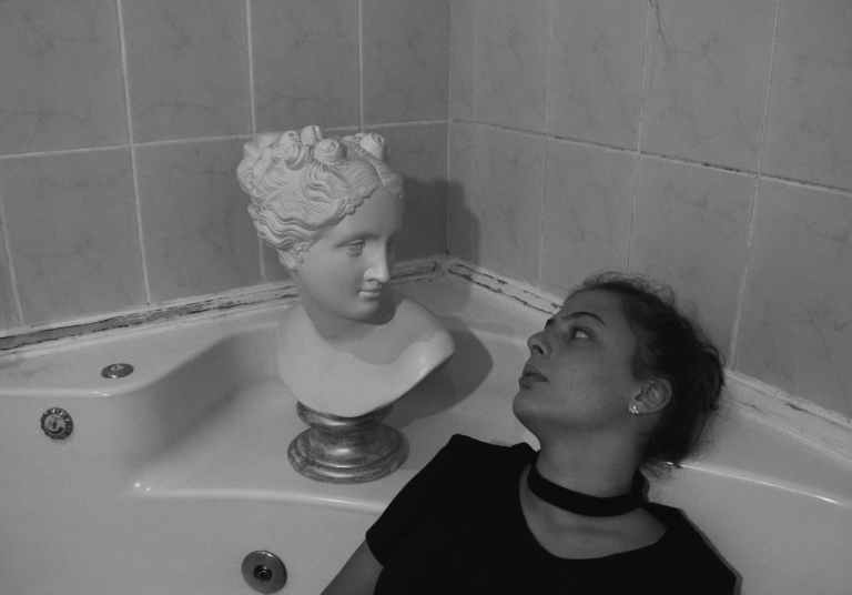 black and white photo of woman inside a bathtub staring at a head bust
