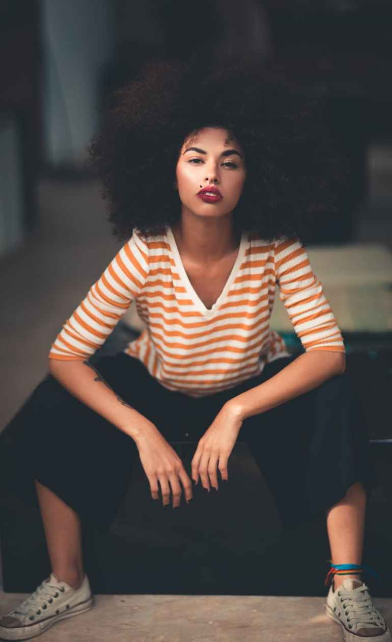 woman sitting wearing orange and white v neck striped elbow sleeved shirt