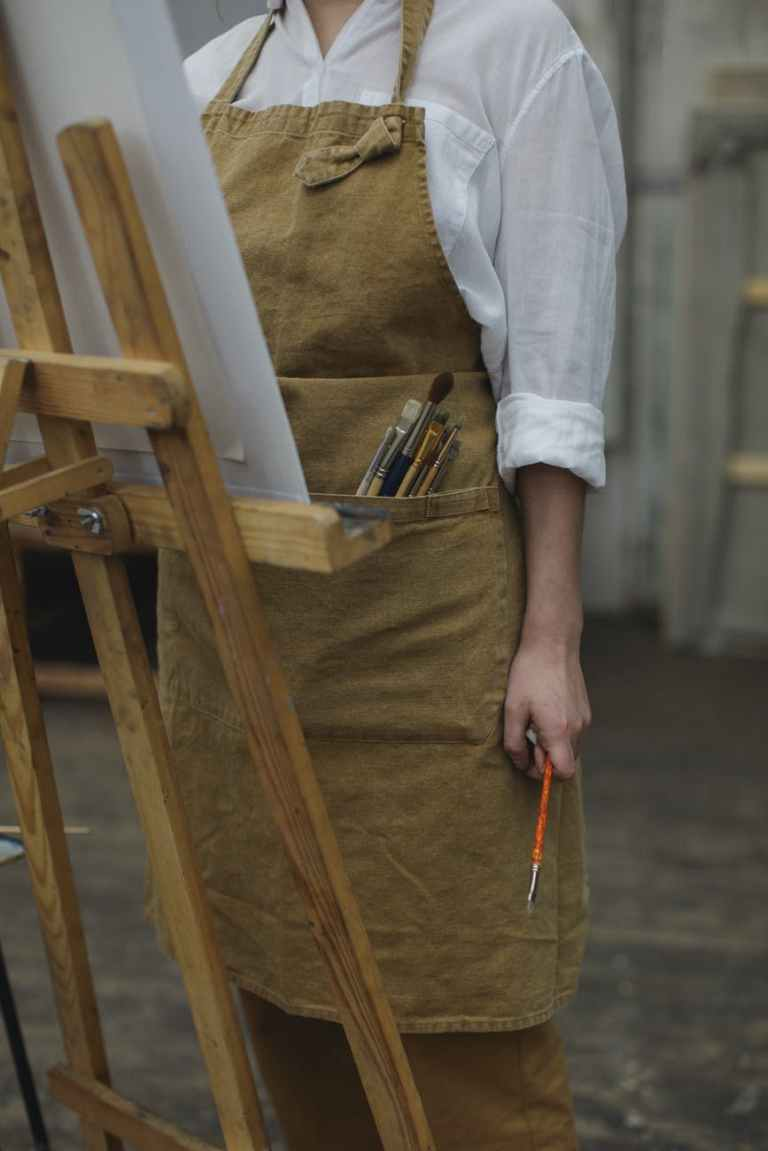 person in white long sleeve shirt holding paint brush