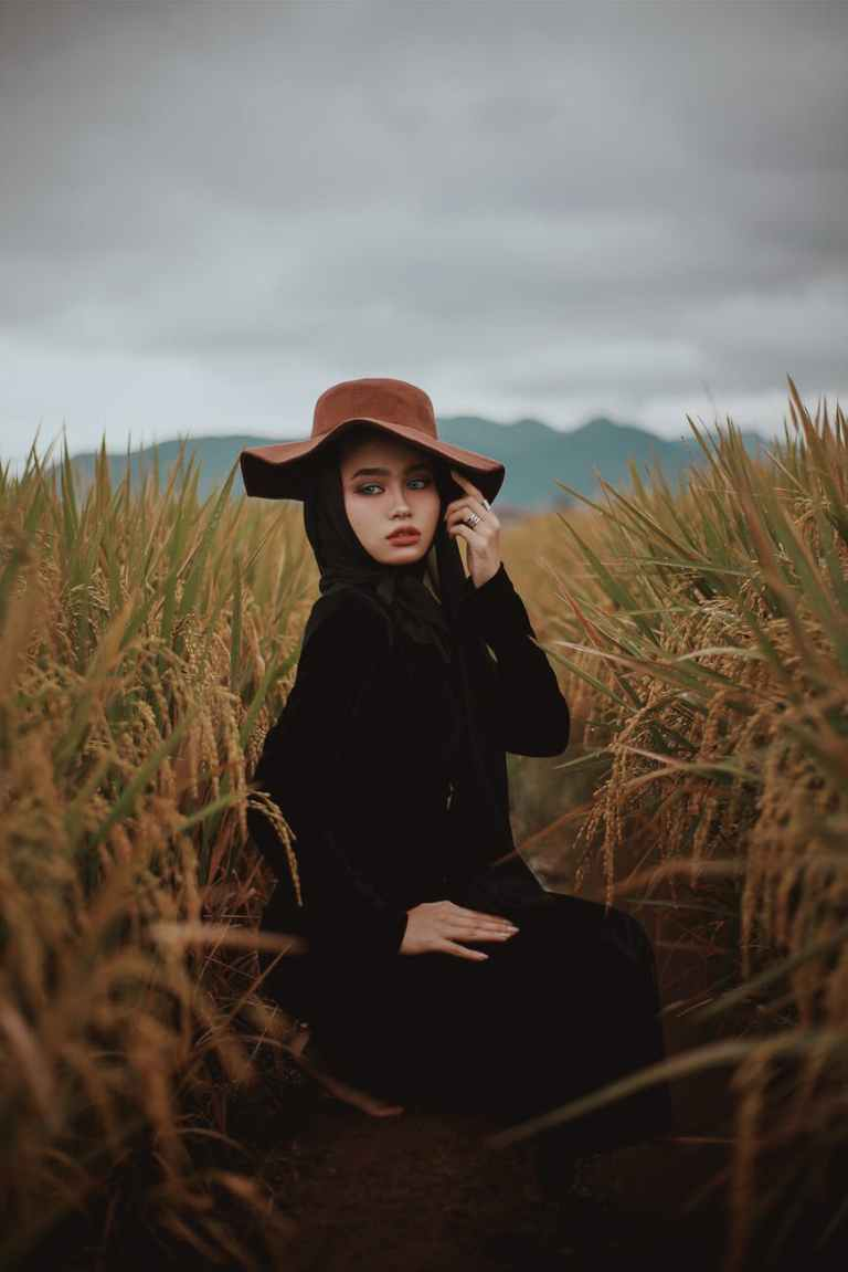 woman in black long sleeve shirt and brown hat sitting on brown grass field
