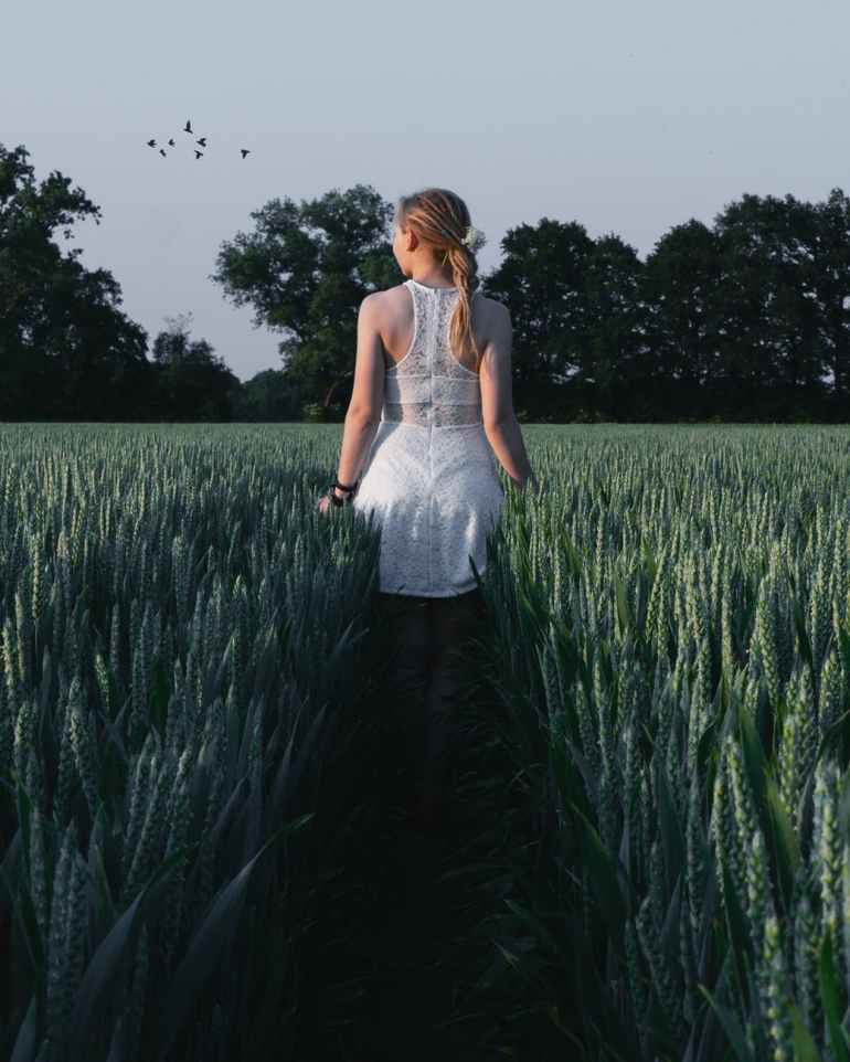woman in white sleeveless dress near green plants