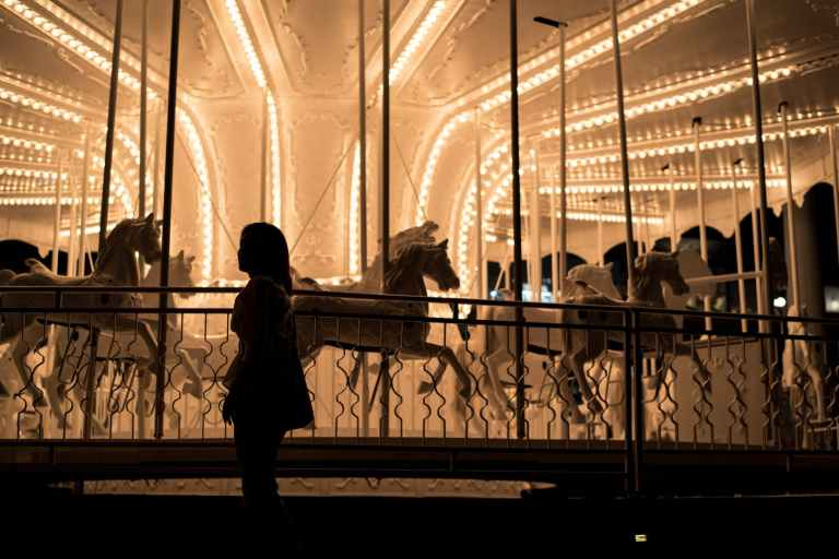 girl standing near carousel