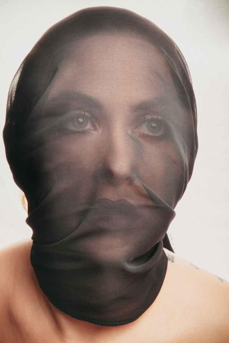 woman covering black mesh mask
