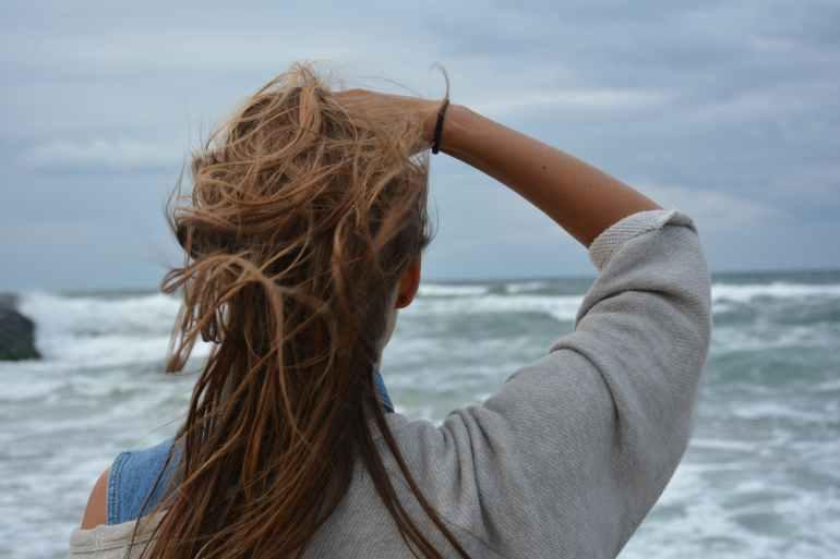 back view hair observing ocean