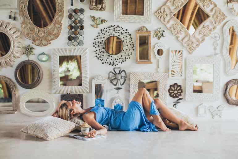 woman lying on the floor near wall mirrors