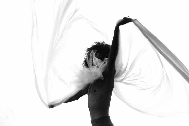 grayscale photography of man swishing mesh veil