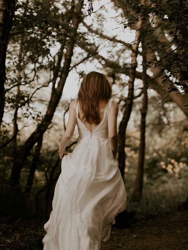 back view photo of woman in white dress walking in the woods
