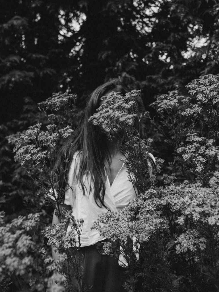 grayscale photography of woman standing near plants and trees