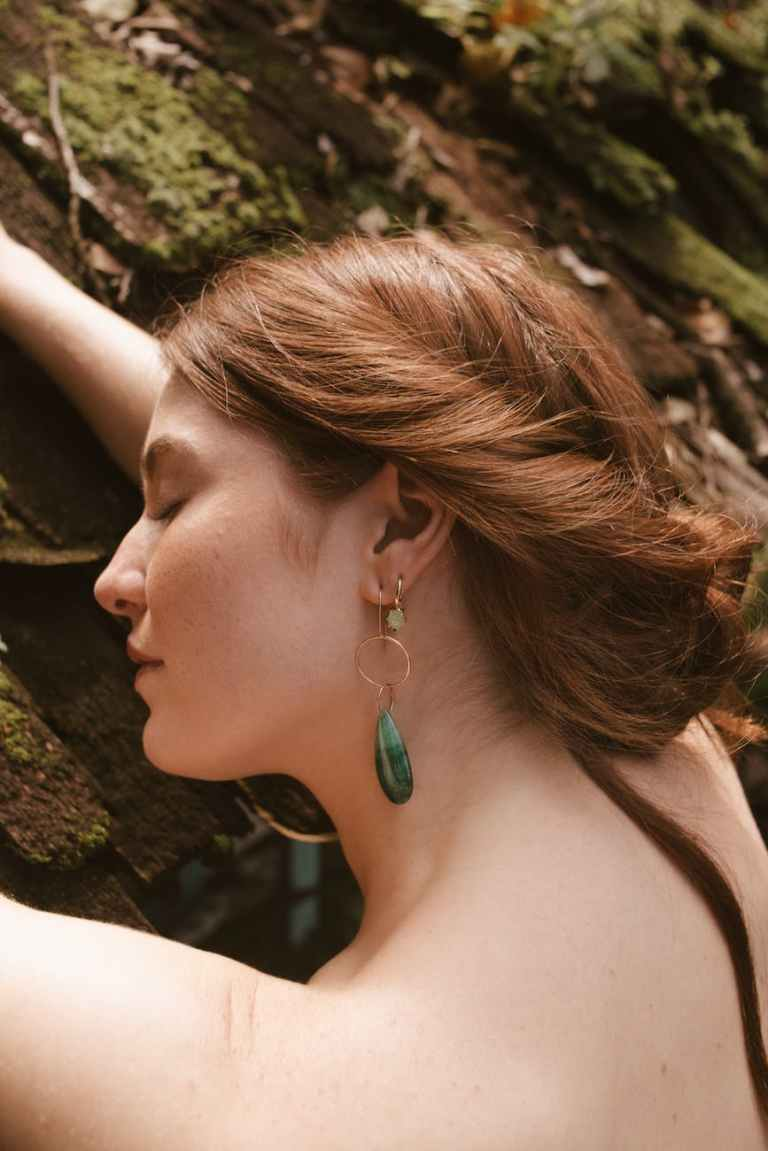 photo of woman wearing green earinggs