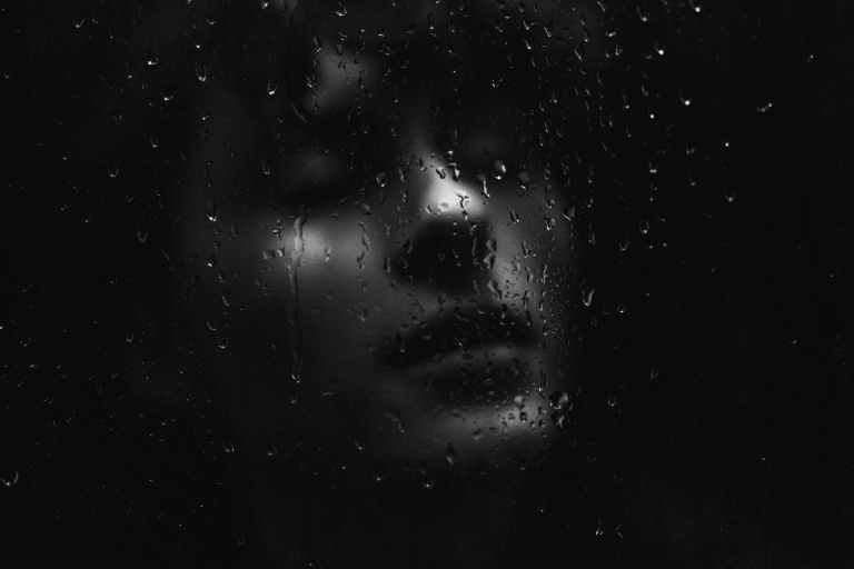 woman face behind wet glass