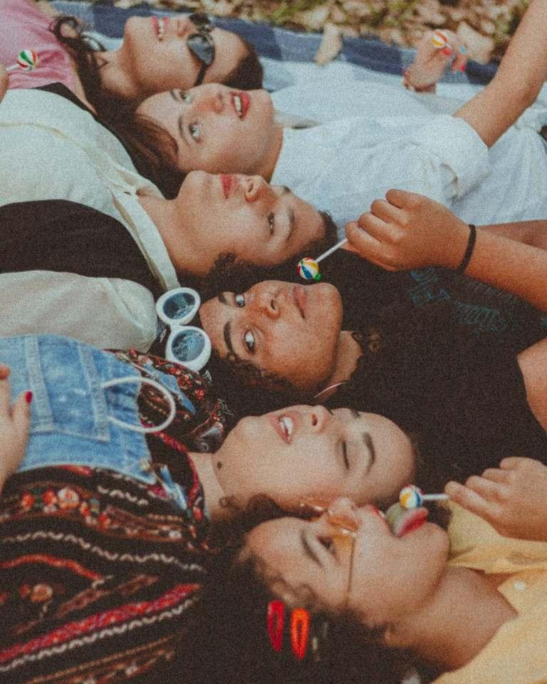 group of woman lying on blanket eating lollipops