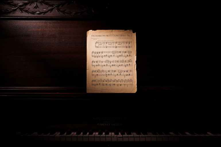 photo of music notes leaning on wooden piano