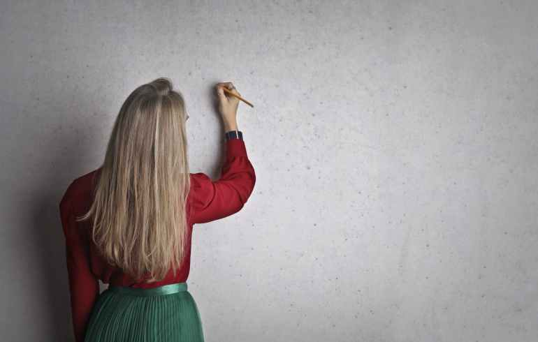 woman taking notes on concrete wall