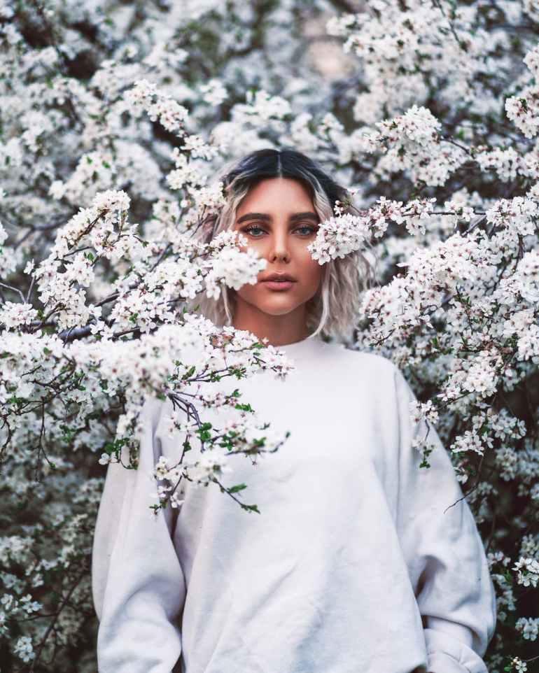 woman ii white long sleeve shirt standing near white flowers