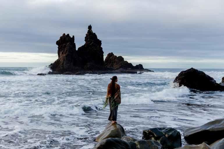 unrecognizable female tourist standing on rocky coast