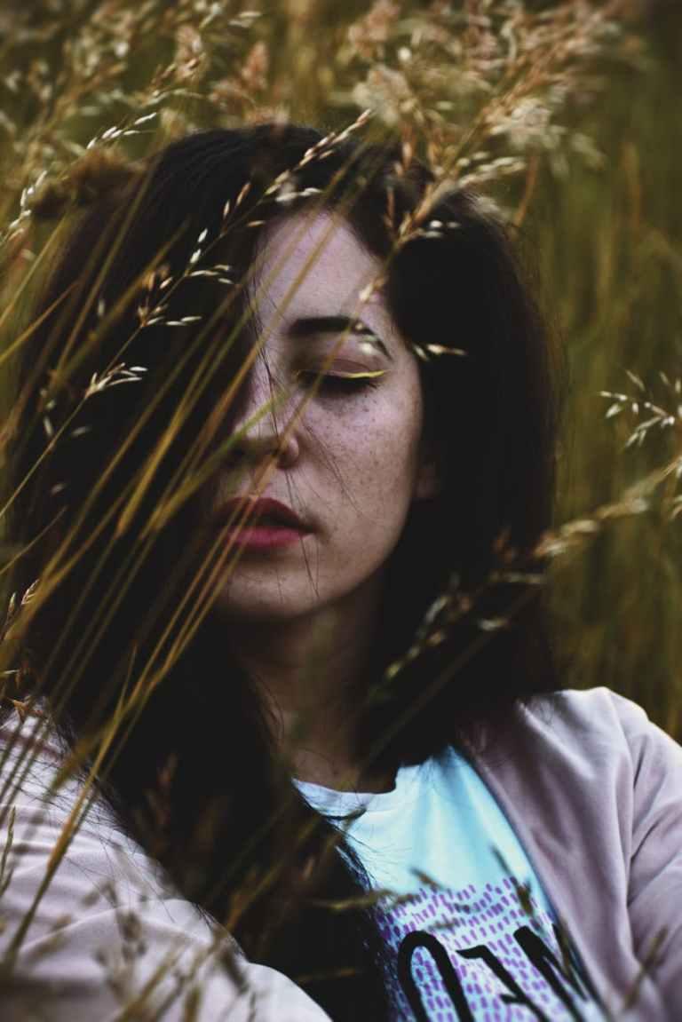 woman behind a grass