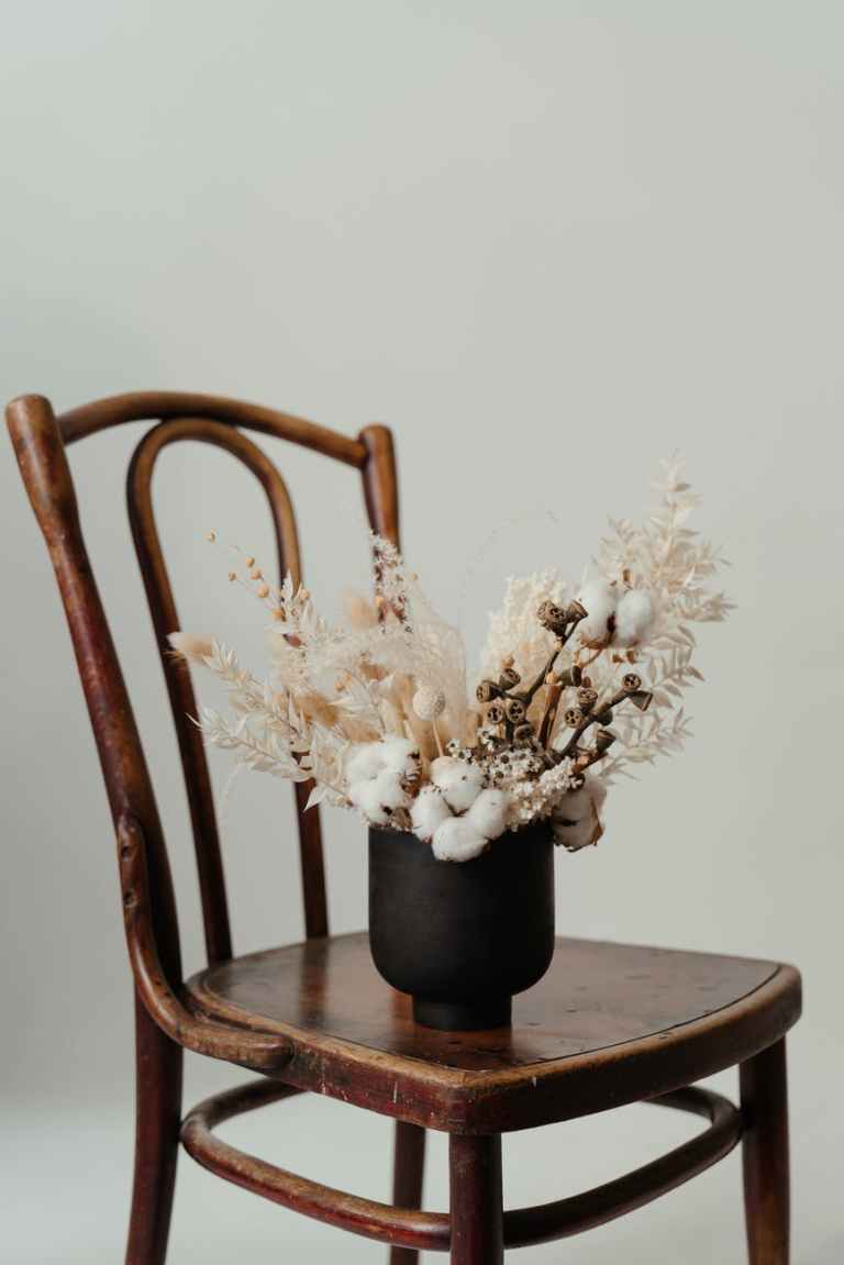 white flowers in black ceramic vase on brown wooden table
