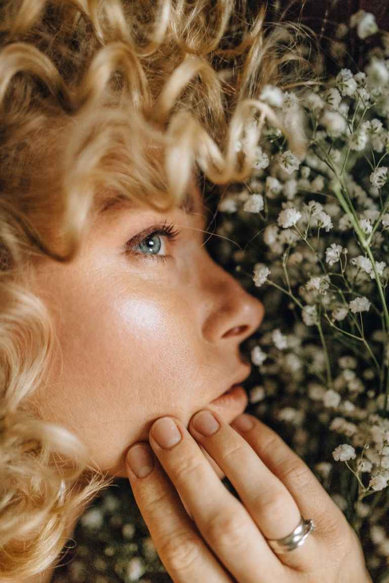 close up photo of woman s face near white flowers