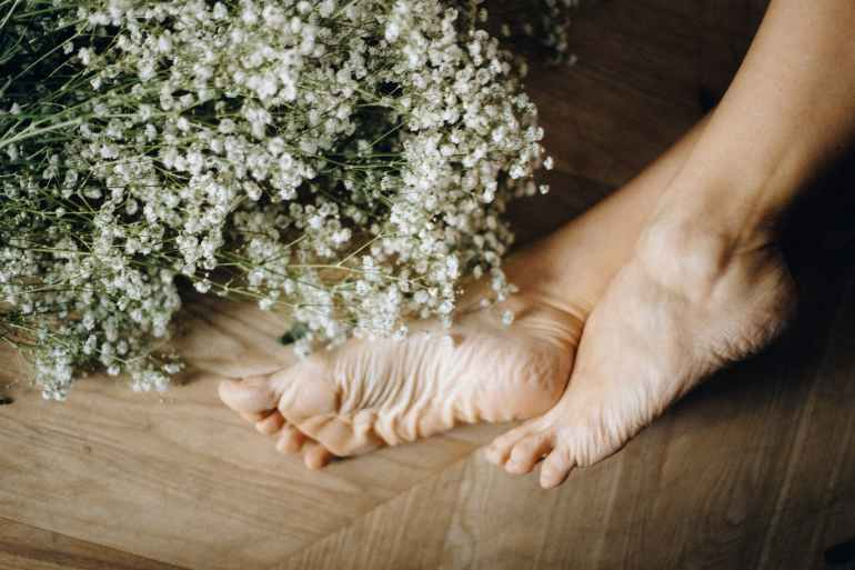 person s feet on brown wooden floor