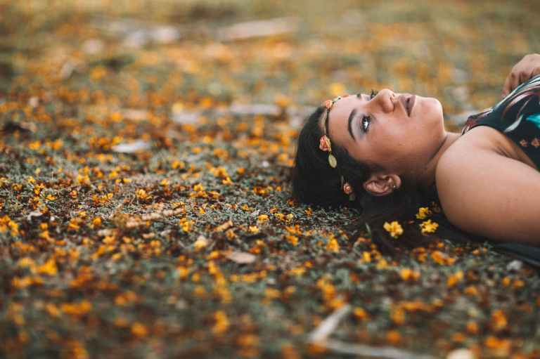 photo of woman in flower crown lying down on the ground