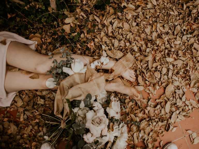 woman legs beside flowers
