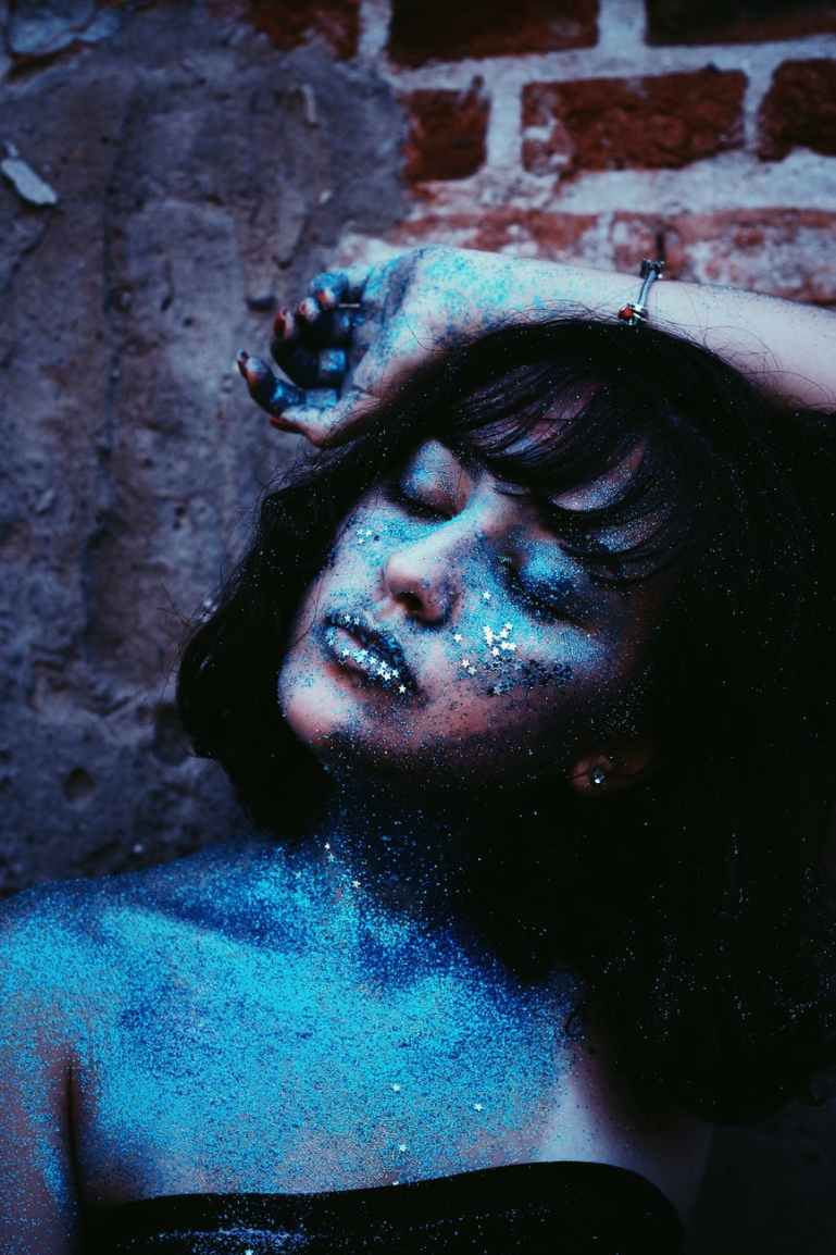 woman with blue glitters leaning on brown wall