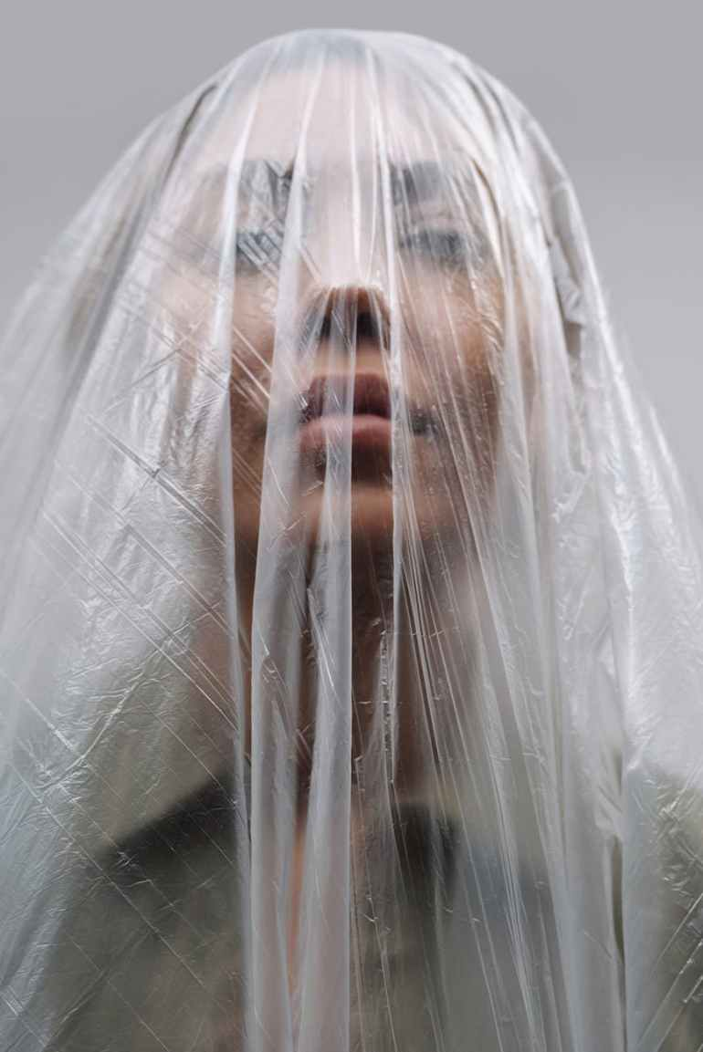 unrecognizable woman covered with plastic bag