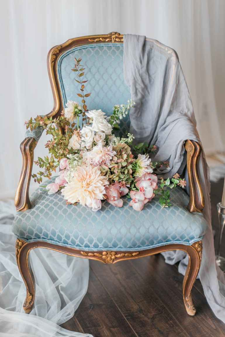 white and pink flower bouquet on blue armchair