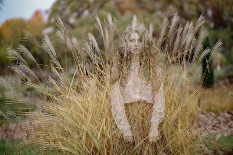 photo of woman standing on wheat field