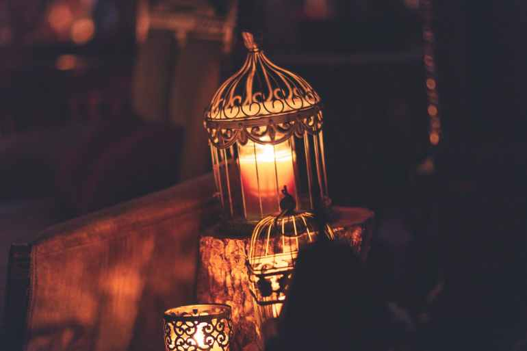brown metal cage with lighted candle