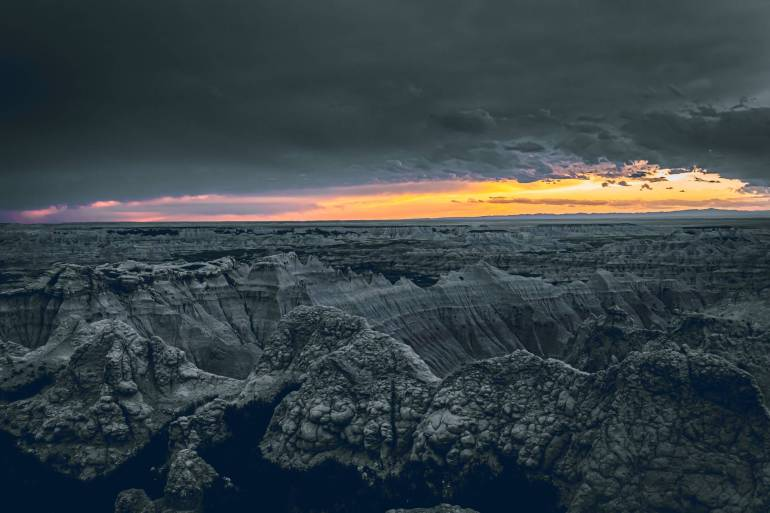 endless mountain terrain under overcast sunset sky