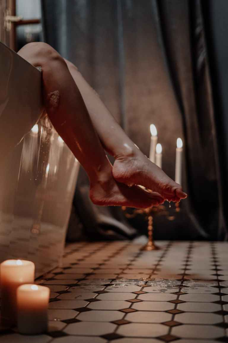 person holding lighted candle on table