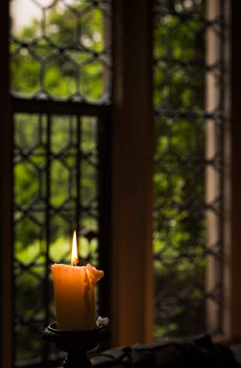 yellow lit candle in candle holder