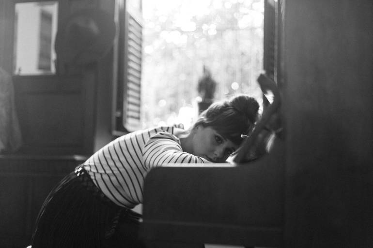 grayscale photography of woman in white and black stripe crew neck top